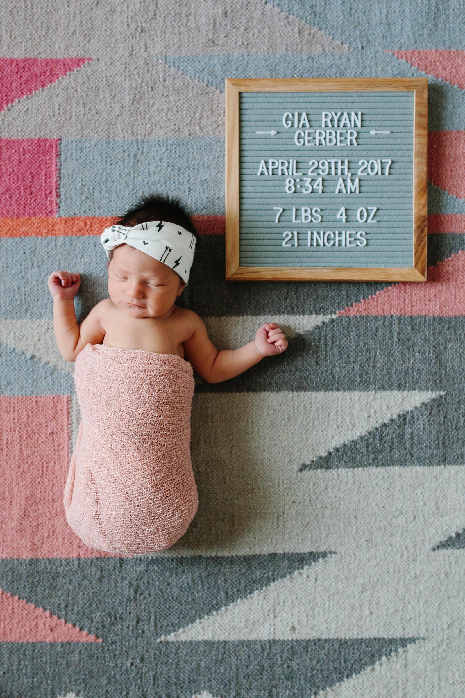 Edmond Oklahoma newborn photos in home, natural nursery baby girl photos laying on rug swaddled.