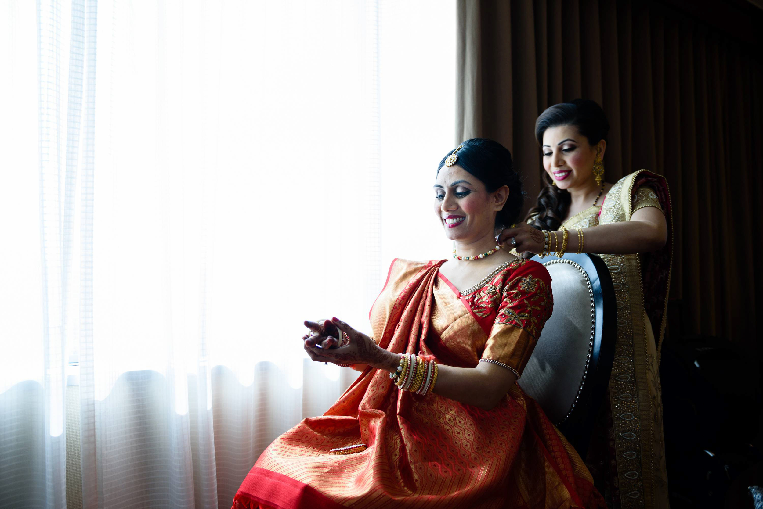 bride getting ready at the sheraton mahwah nj. This image captures a very sweet moment between the bride and her sister helping her getting ready.