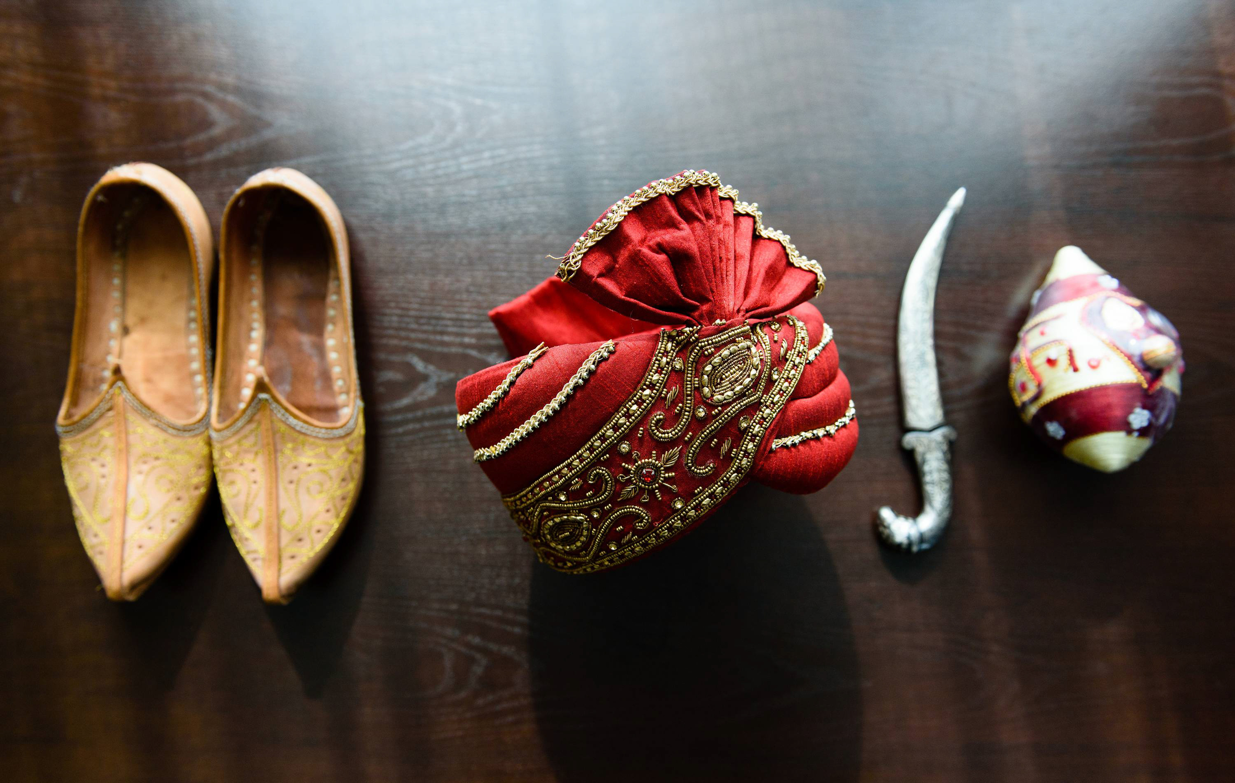 traditional indian wedding shoes for groom & accessories such as safa or sapaa, decorative coconut and khanjar/dagger.