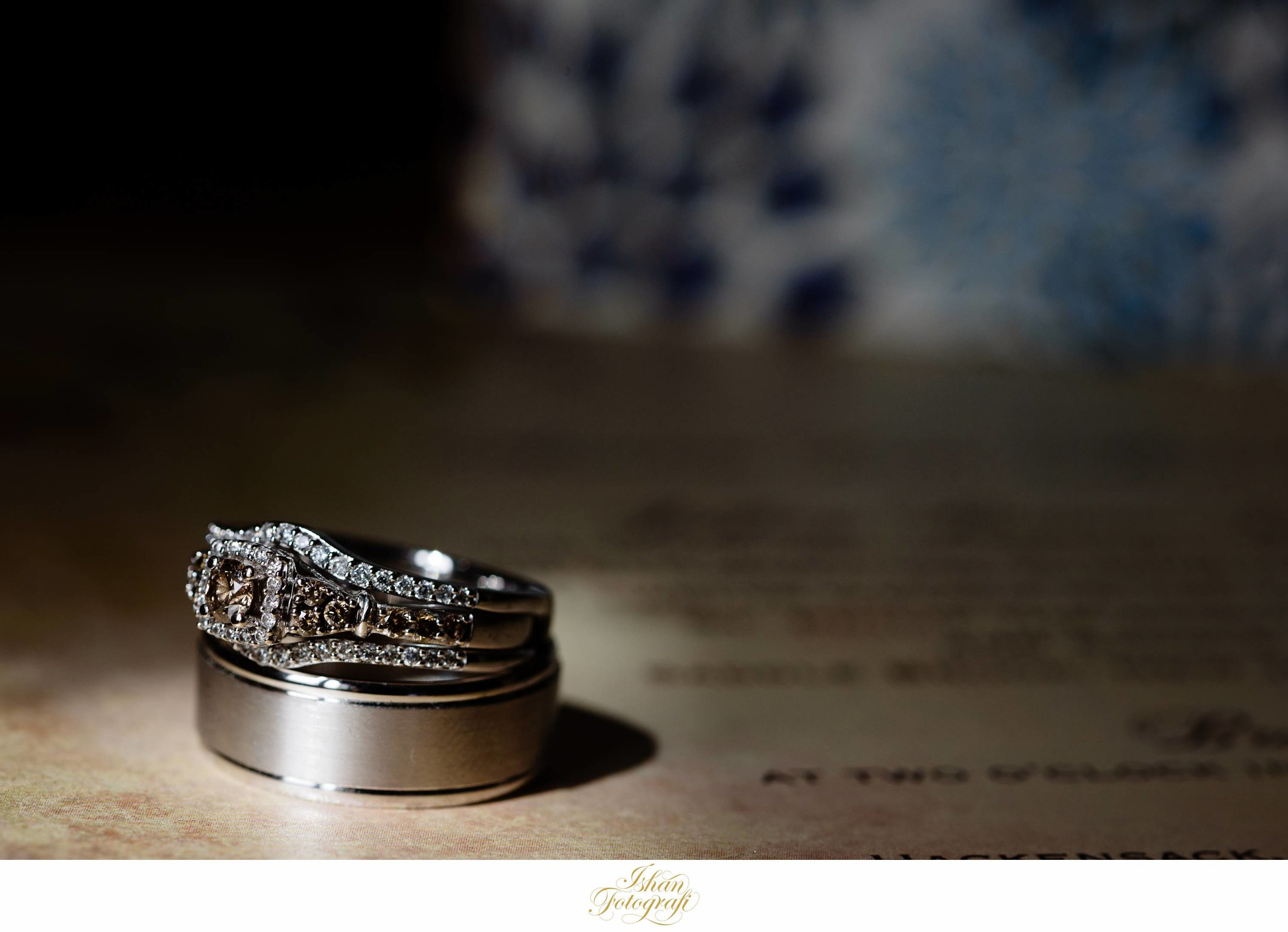 Amanda's stunning engagement ring &Jeffrey's wedding band placed over their invitation cards. We love incorporating personal items while photographing details.