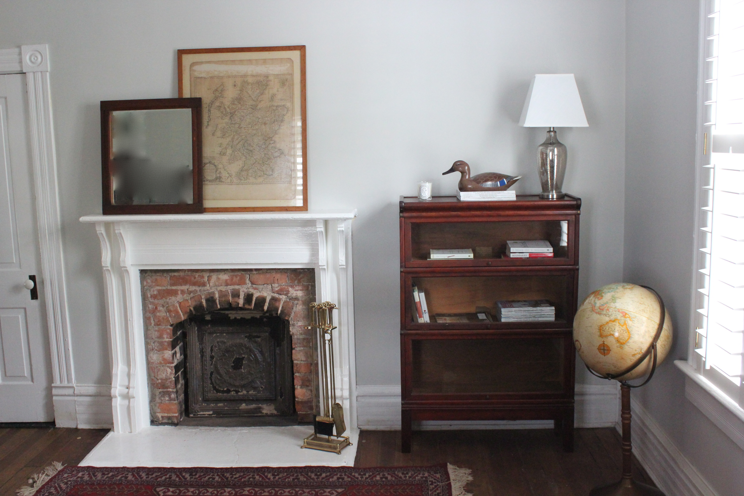 This is a corner of their house where I put most of my items. On the mantle is a map of Scotland dated from 1776 ($498) behind an Eastlake style wall mirror ($275). In front of the fireplace is a set of brass fireplace tools ($275). Next to the window is a vintage Replogle floor globe ($298). In the corner is a Globe Wernicke three stack barrister cabinet ($650). On top of the barrister cabinet is a hand painted duck decoy ($98).  On the floor is a vintage Persian rug ($375).