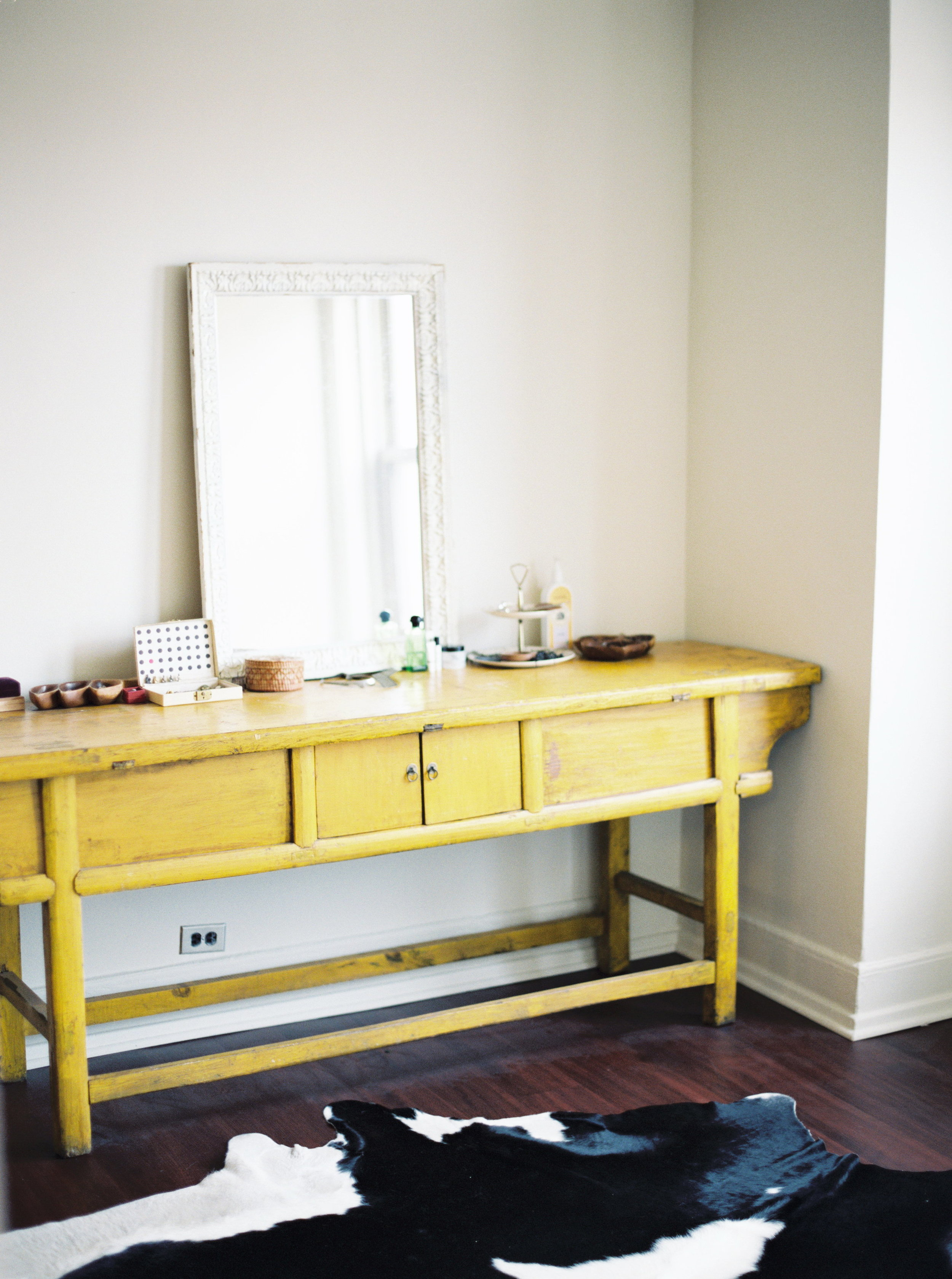 """We call this piece of furniture the """"yellow thing."""" It was one of our first major furniture purchases after we got married. We found it at Atlanta's Lakewood Antique Market (when it still existed!) and fell in love. It is from Mongolia and was purportedly usedin a kitchen as a countertop  it has wonderful marks and dings, and the color is alsooriginal. When we first bought it we lived in a 900 sq. ft. apartment and the kitchen had noreal countertop, so that is what we used it for as well! The white mirror on top is abeautiful antique that my mom gave me."""