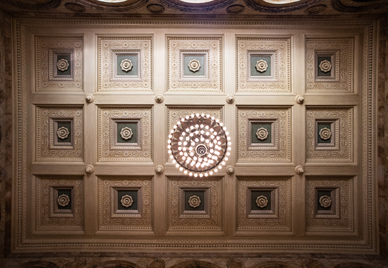 A view of the double coffered ceiling and the great chandelier above the grand staircase in the Boston Public Library.