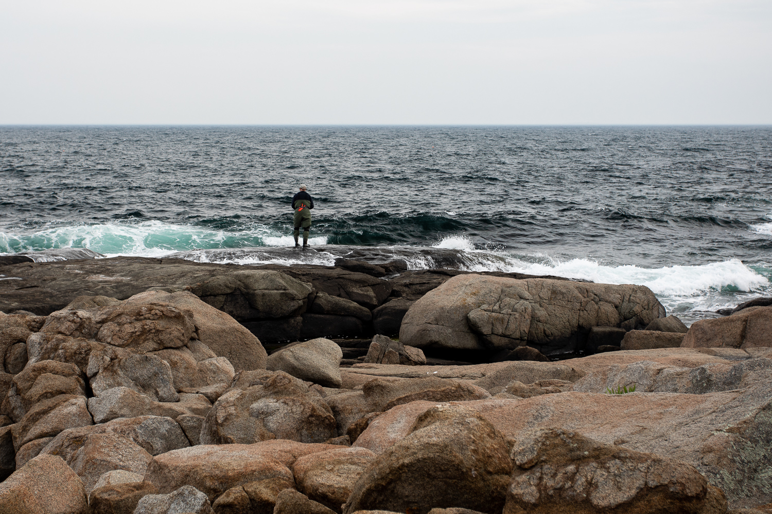 A lone fisherman on the rocks at Nubble Point in York, Maine.