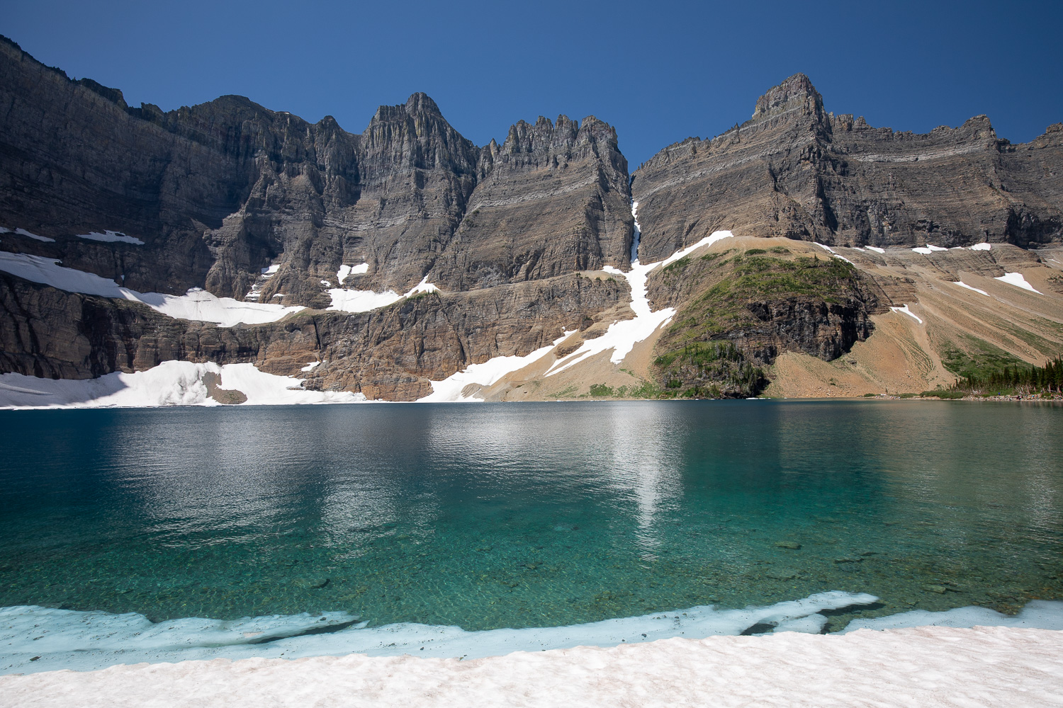 A view of Iceberg Lake from an unmelted snow patch.
