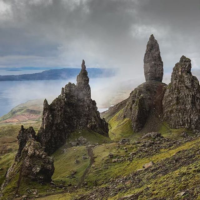 """One of the most picturesque areas in Scotland: the Storr on the Isle of Skye. ⠀  There is a Scottish legend that the Old Man of Storr was a giant who resided on the Trotternish Ridge. When he was laid to rest upon his death, his thumb protruded above the ground—this is the """"Old Man of Storr."""" The Old Man of Storr rises about 50m above the surrounding landscape. ⠀ One of the most incredible sights to witness here was the drastic change in weather and fog conditions—the entire landscape could be clear one moment and a few minutes later be completely obscured by fog. ⠀ For this frame: the fog was starting to arrive and our group was taking turns climbing that rock at the bottom left corner. Look closely—can you spot @charlottelittlewolf down there? ⠀ I'll be posting more photos from Scotland 🏴 this week."""