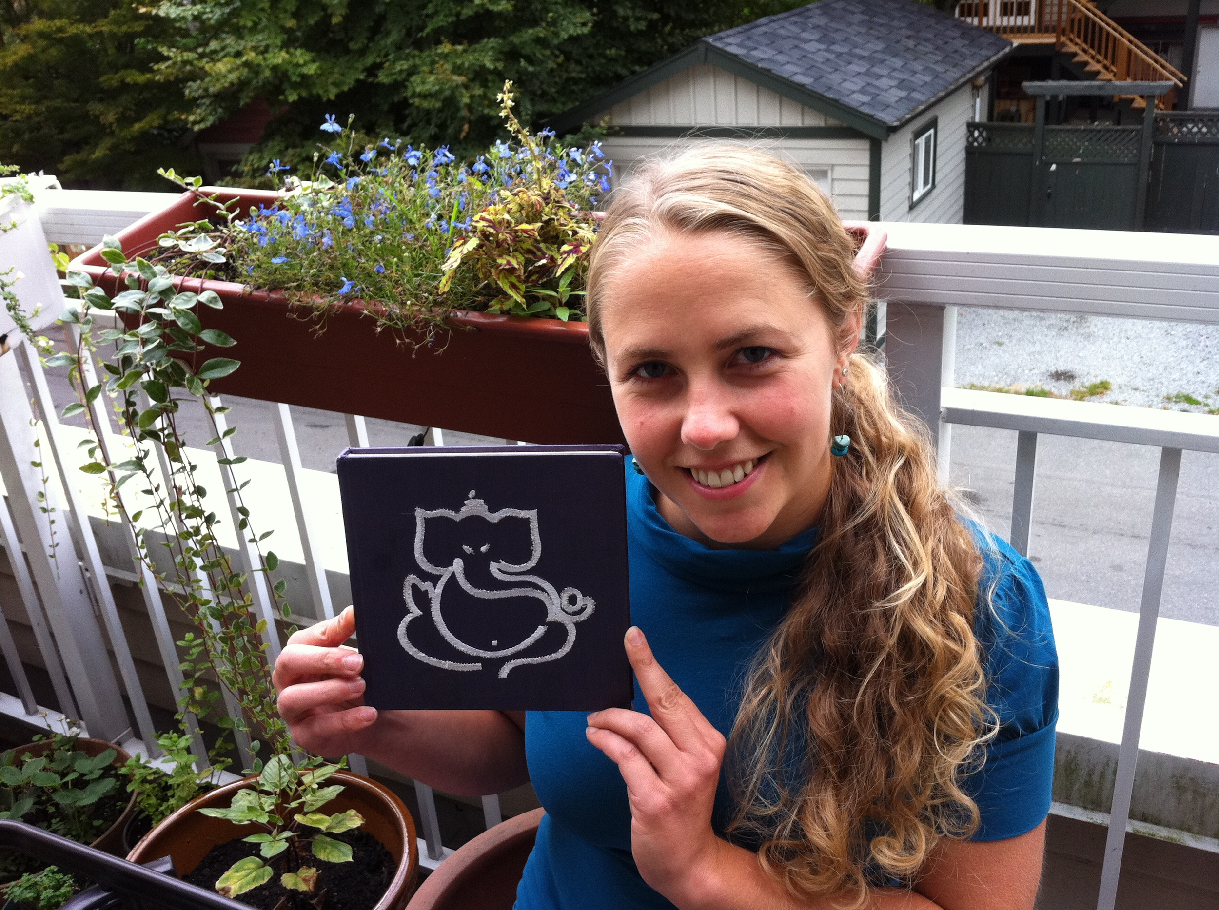 """Here is Kate with the """"traveling mantram book"""". This notebook is making its way to YAs around the world and each YA is writing lines of their mantram in the book. Read more about the mantram  here !"""