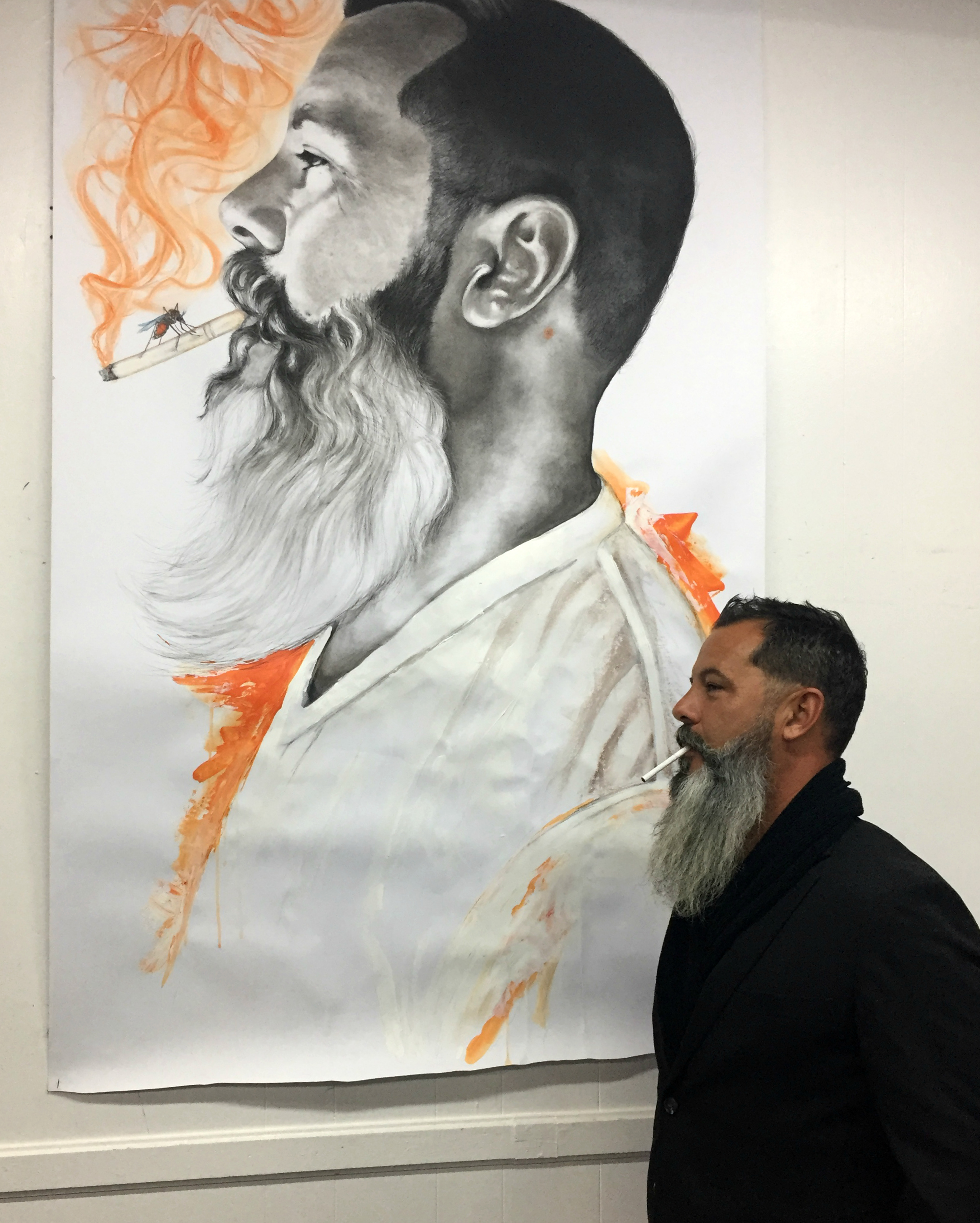 Artist Anthony Hernandez in front of a portrait created by Anthony Burks Sr. To view more of Burks work, please visit https://www.anthonyburkscollection.com/