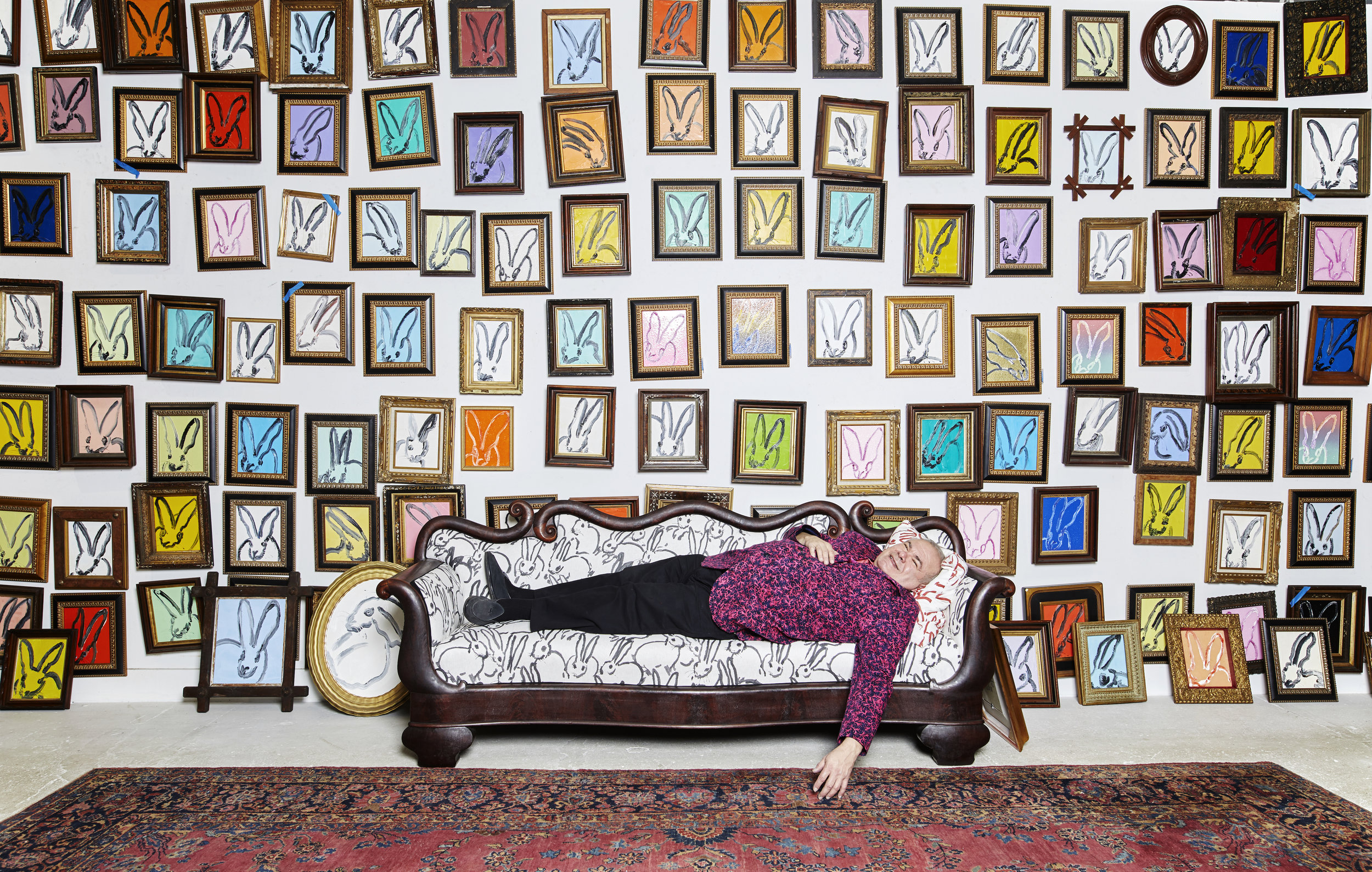 Portrait of Hunt Slonem in his studio, on his bunny couch in front of his Bunny Wall, Brooklyn, New York. Photograph by Brandon Schulman.