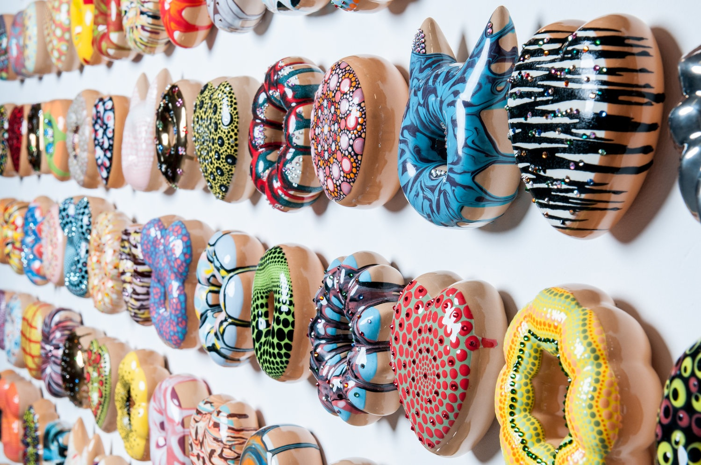 Donut think to much, Be Happy;  Artist:  Jae Yong Kim; ceramic, under glaze, glaze, luster glaze, Swarovski crystals; Installation size: 66 x 80.5 x 1.5 in. 2013-2017 Courtesy photo by : Anthony Brunelli Fine Arts