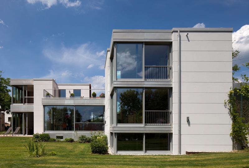 Das Grundstück befindet sich in leichter Hanglage mit Ausblick auf den etwa 60 Meter tiefer gelegenen Wörthsee. Der gegliederte Baukörper schafft die Teilbarkeit des Hauses in zwei unabhängige Einheiten, was mehreren Generationen ein voneinander unabhängiges Wohnen ermöglicht.  >>>>