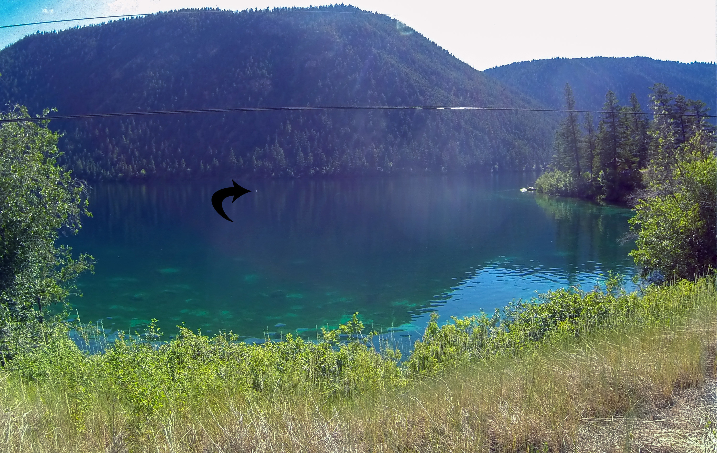 Arrow marks the diver's float and descent line to the microbialite structures. The float is close to the middle of the lake