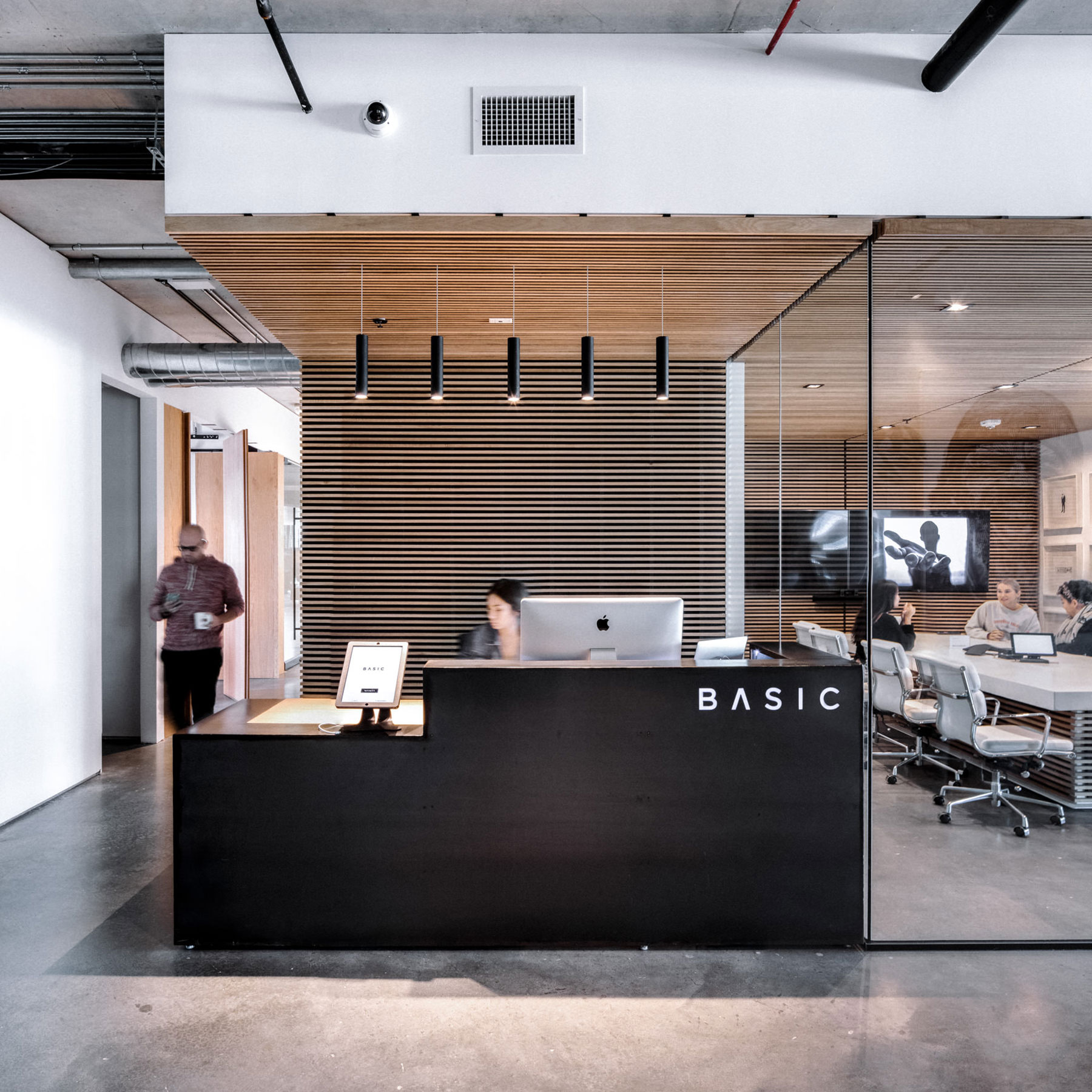 ENTRY - Upon entry, large blackened steel reception featuring integrated BASIC branding is flanked by two large conference rooms with custom slat trim.