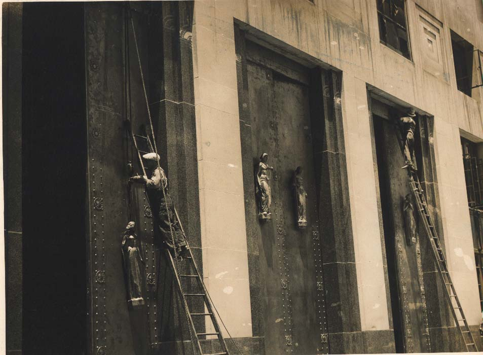 """Two workers installing the doors of the Davidson County Courthouse"""