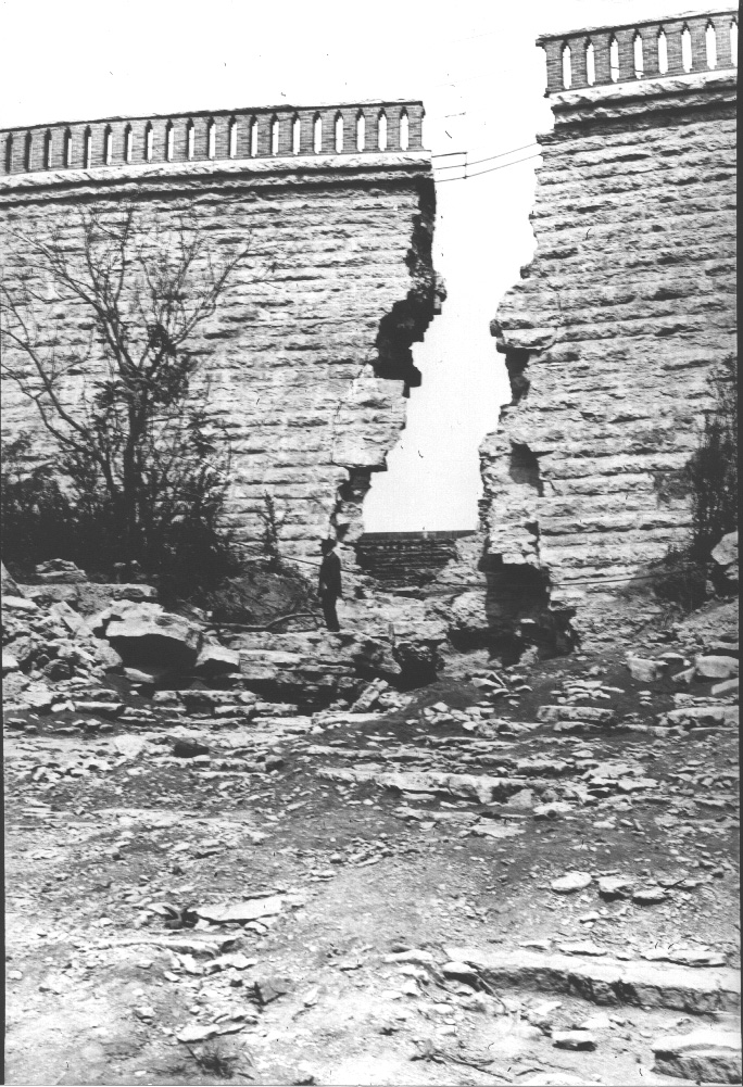 """Man standing on debris near a breach in the Nashville Resevoir wall. 1912"""
