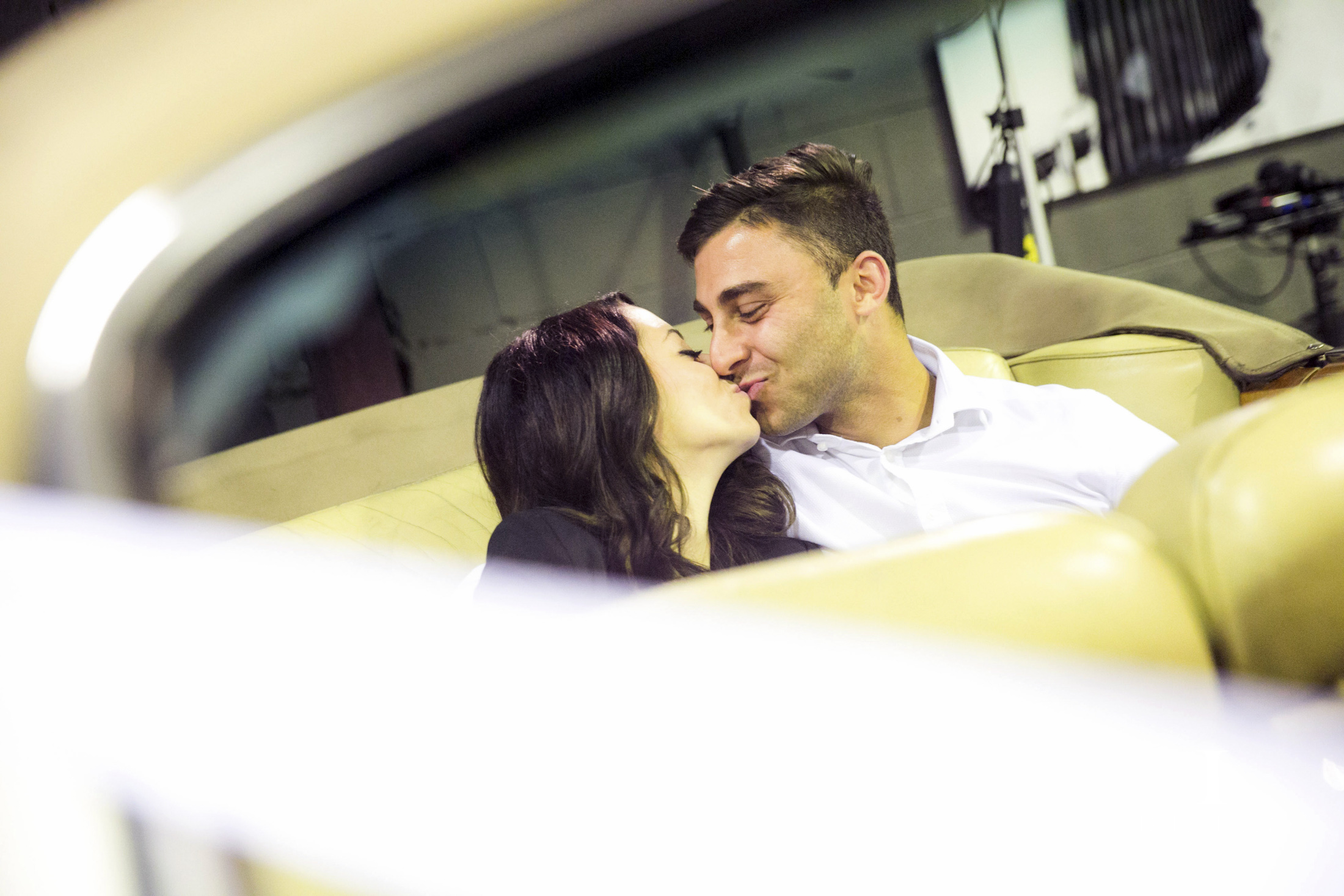 An Engaged couple share a kiss in the back of  a Rolls