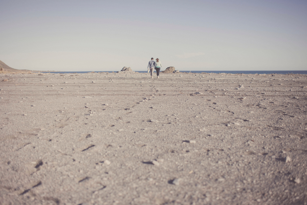 Rugged desolate sea/ landscape with couple walking away from camera in the middle. By jenny Siaosi.