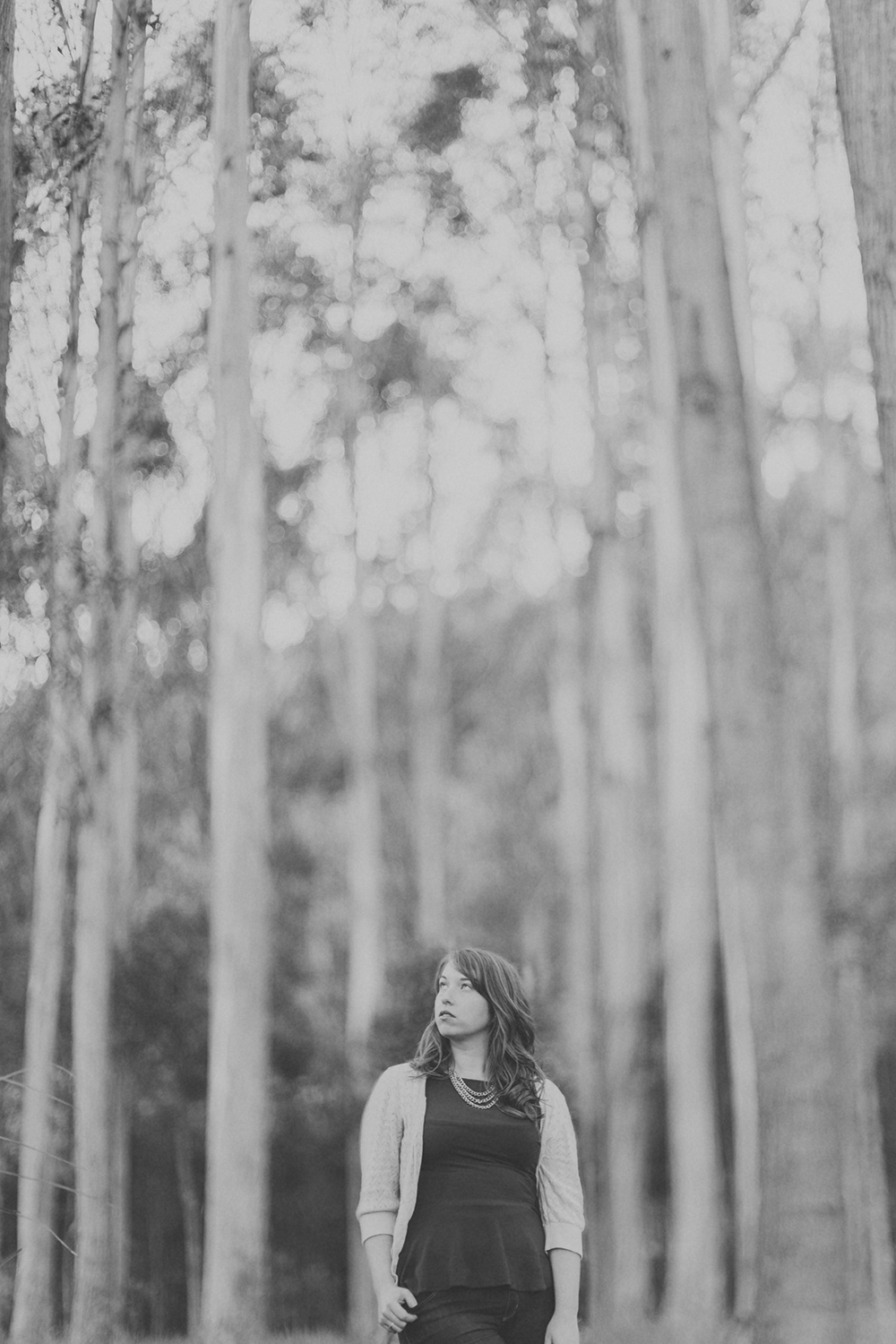 Woman looks up toward tall trees in eucalyptus forest. NZ. Photography by Jenny Siaosi.