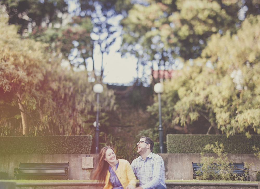 Laughter on an engagement photo shoot with lens flare and freelensing. Photo by Jenny Siaosi.