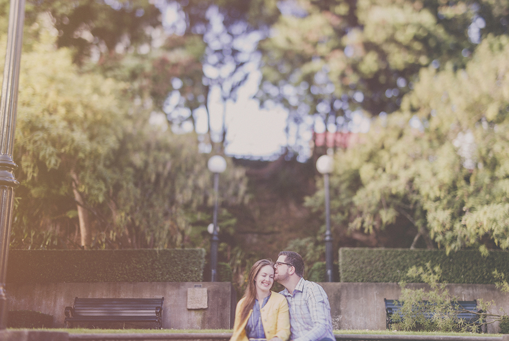 Laughter and a sweet moment shared on an engagement photo shoot with lens flare and freelensing. Photo by Jenny Siaosi.