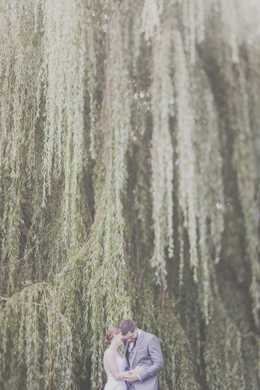 Bride and Groom embrace under Willow tree with dripping leaves. Photo by Jenny Siaosi.