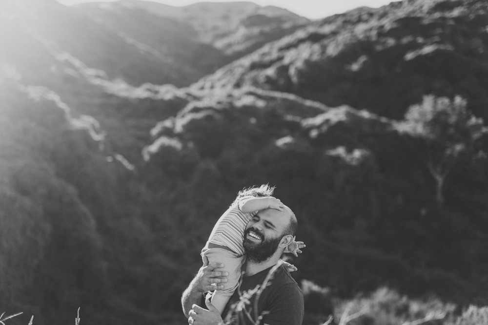 Happy portrait of dad with daughter on his shoulders playing. Wellington NZ. By Jenny Siaosi.