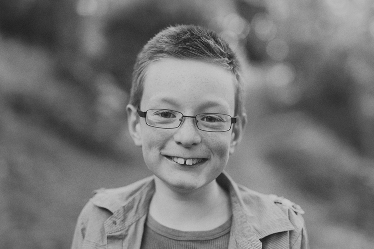 Black and White photo of young boy smiling at camera.