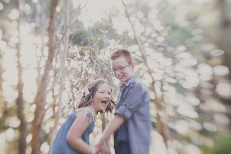 Natural photo kids laughing and playing with each other in the trees. Photo by Siaosi Photography.
