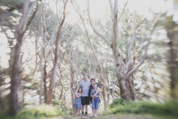 Natural (lens baby) photo of family amongst the trees. Photo by Siaosi Photography.