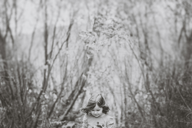 Little girl playing in trees, looking down, black and white photo by Jenny Siaosi.