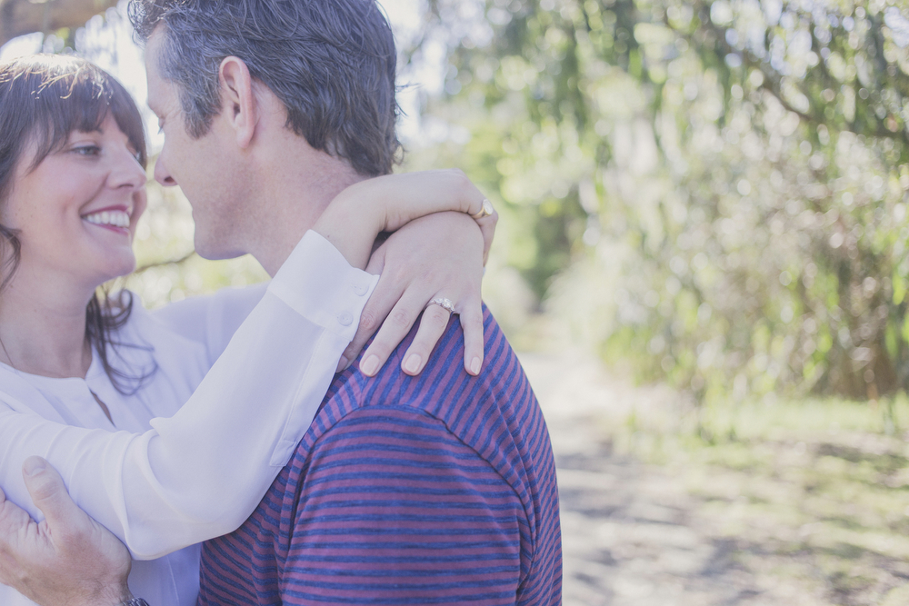 Engaged couple embrace, focus is on the engagement ring. Engagement session in Kapiti, NZ. Photography by Jenny Siaosi.
