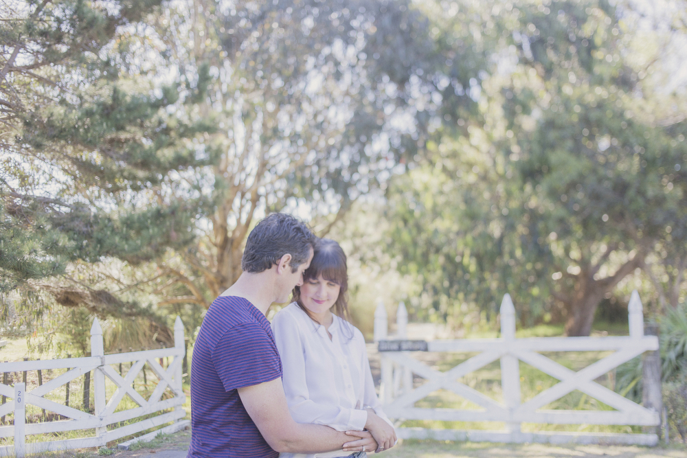 Engaged couple embrace, photographed using a freelensing technique. Which messes around with the plane of focus in a cool way. Engagement session in Kapiti, NZ. Photography by Jenny Siaosi.