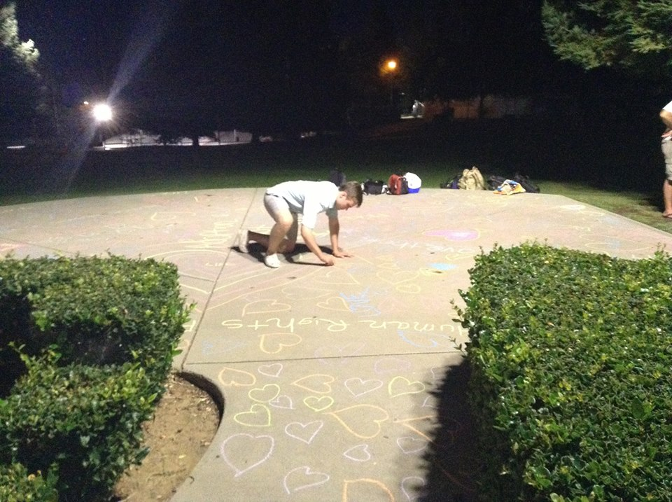 Brady's friend, Patrick, plastering the walkway with facts about abortion