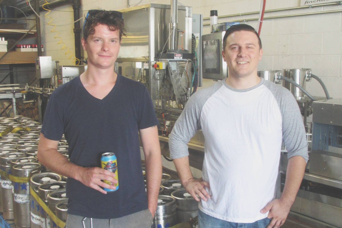 Steven & Bart standing proudly next to Finch's canning line.
