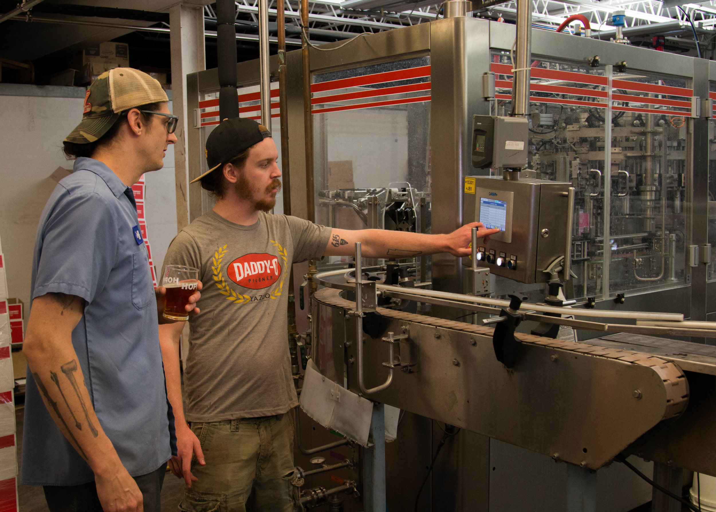 Head Brewer Jeff Burnett (left) advises the next move on the bottling line.