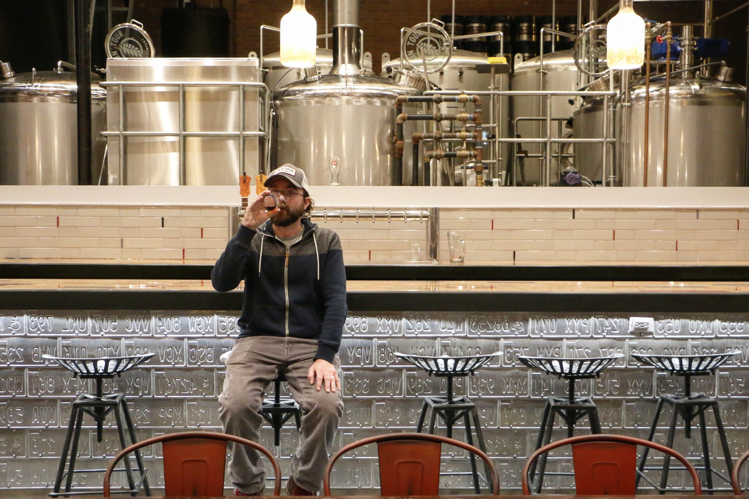 On Tour founder, Mark Legenza, sips a brown ale just prior to the opening of their taproom early '17