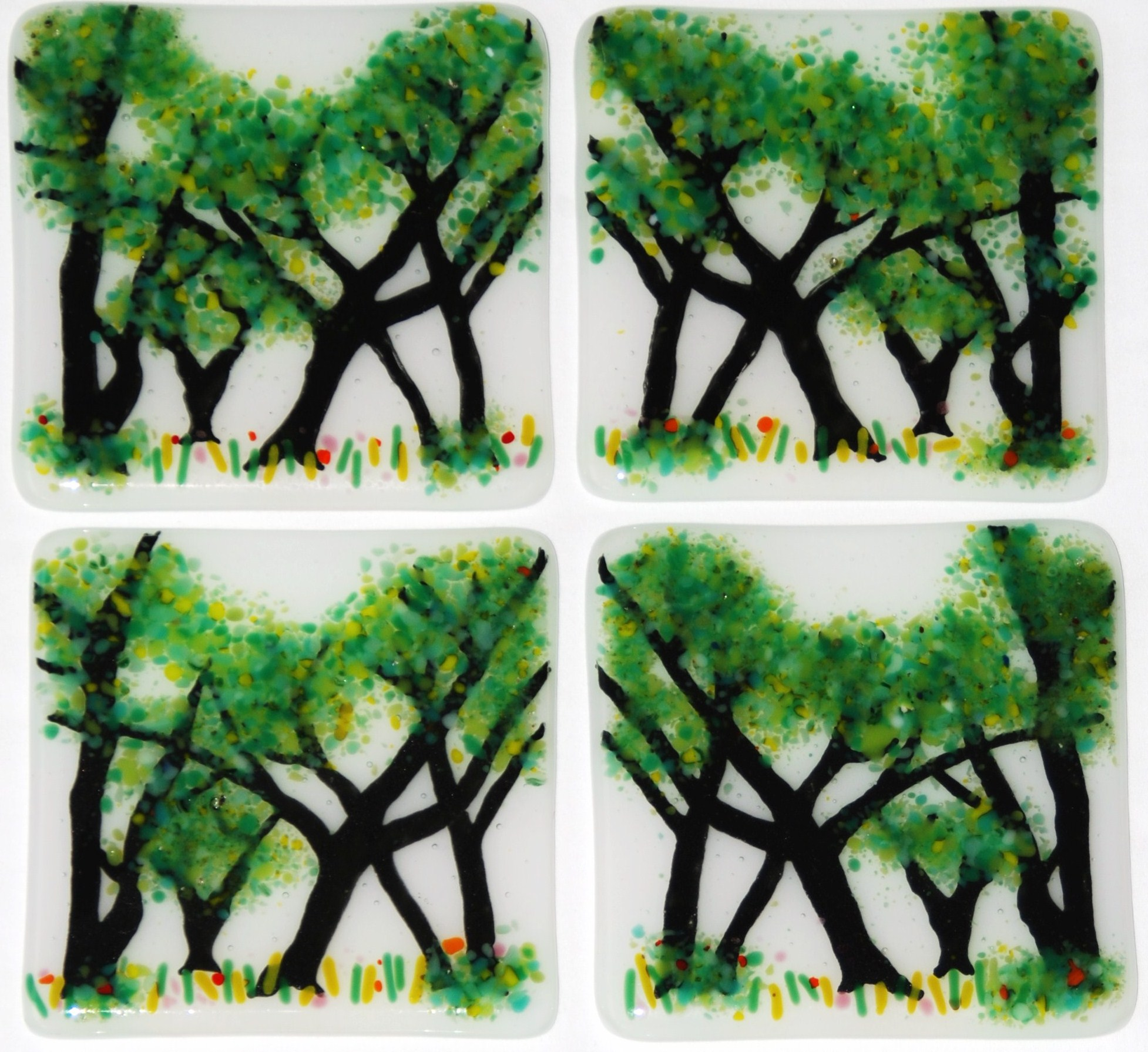 Four hand-painted fused glass tiles with lush trees and hints of summer flowers.