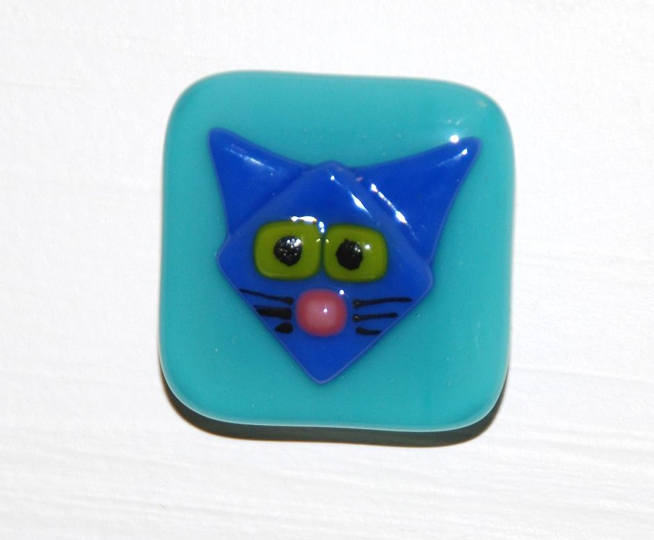 "Blue cat on an aqua blue glass cabinet pull. 1-3/4""."
