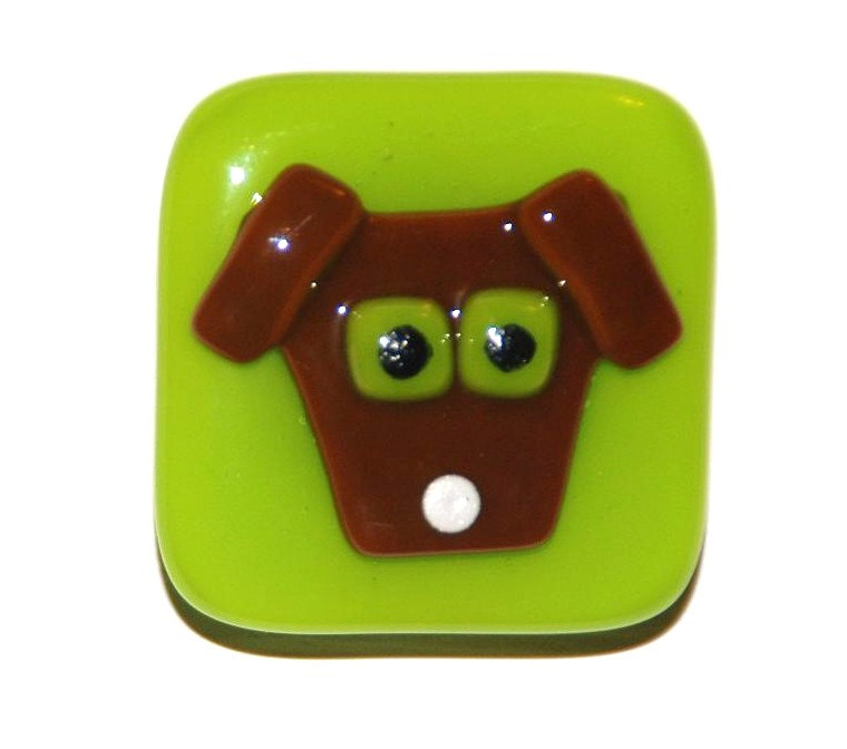 A brown dog with spring green eyes on a matching green glass knob.