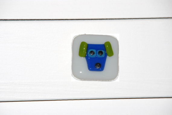 A blue and green dog on a white glass cabinet pull. Dogs and backgrounds can be custom made in just about any colors.