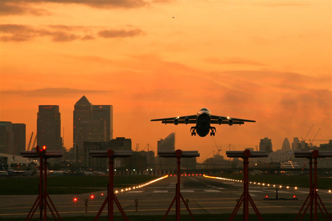 Aircraft taking off from London City Airport at sunset