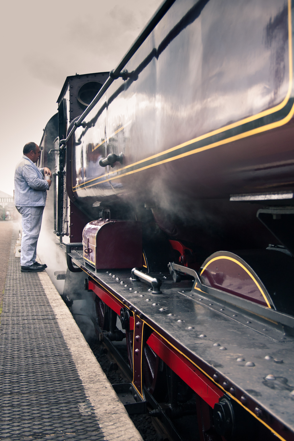 An engineer stands next to a steam train