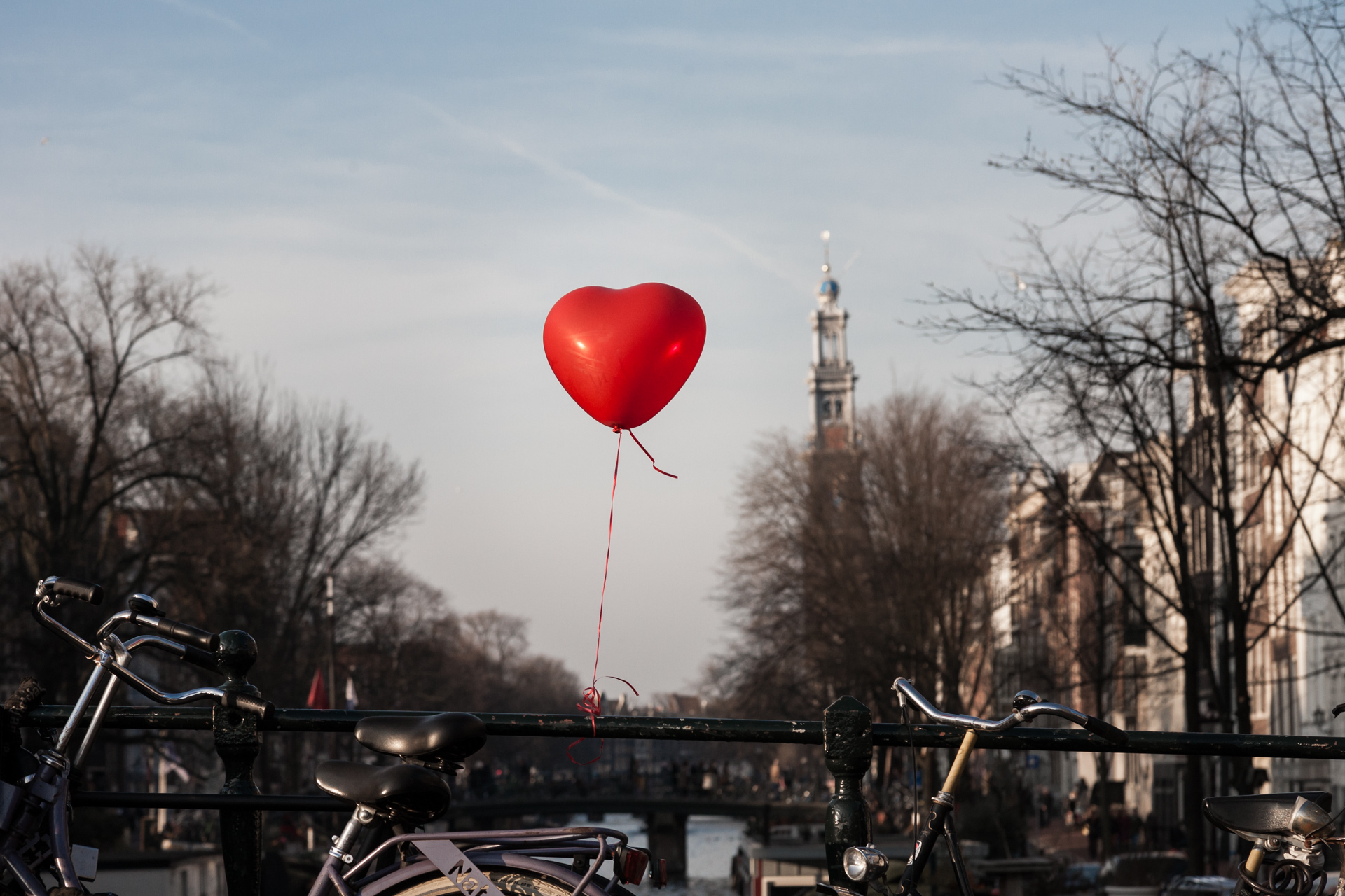 A heart-shaped balloon tethered to a bridge in Amsterdam