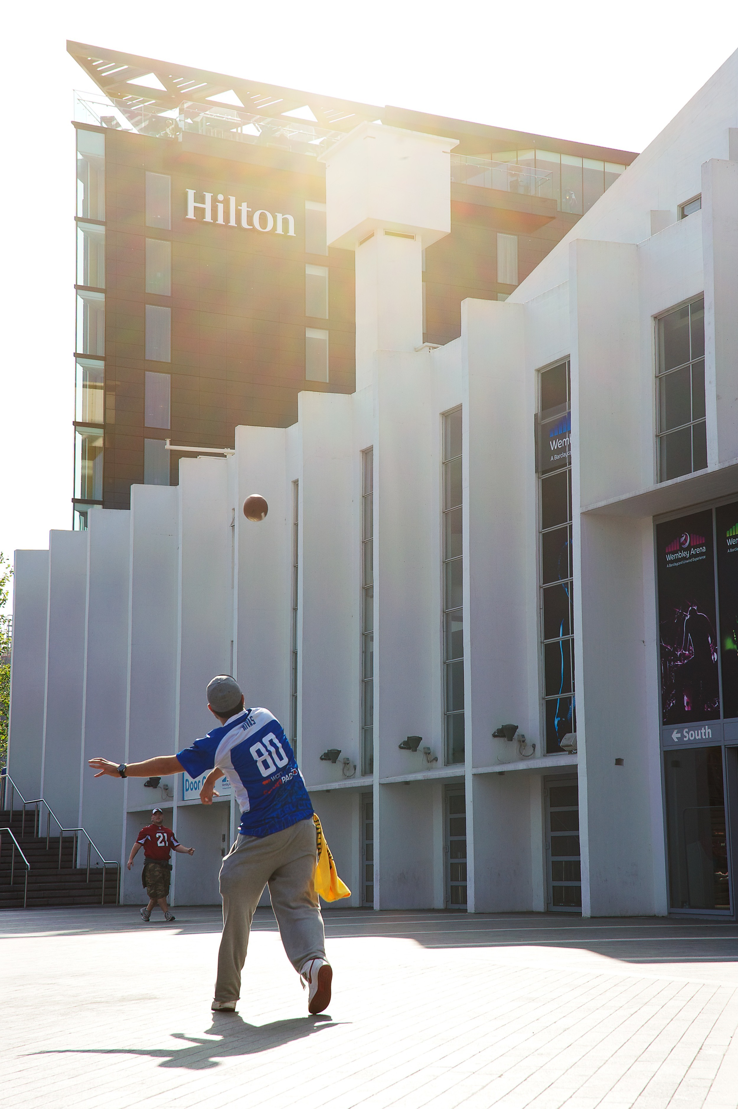 American football fans play in front of The Hilton Hotel for a lifestyle shoot in Wembley during an NFL match
