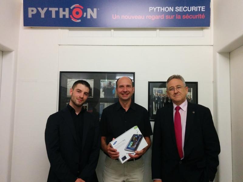 Monsieur Jean-Pierre Garnier (au centre) reçoit le SAMSUNG Galaxy Note de Monsieur Kevin Cordeiro (NODE, à gauche) et de Monsieur Christian Python (Python Sécurité Sàrl, à droite).