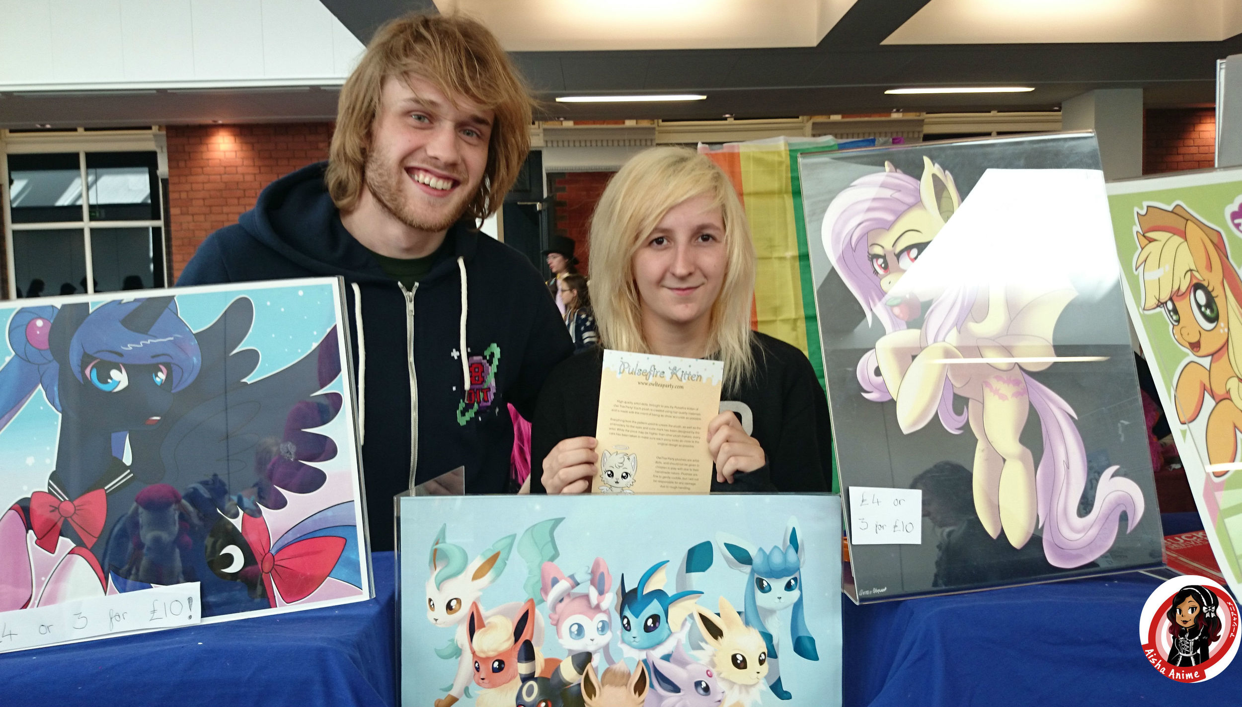 Pulsefire Kitten creator and partner posing with her leftover art as all her plushies sold out Friday night !