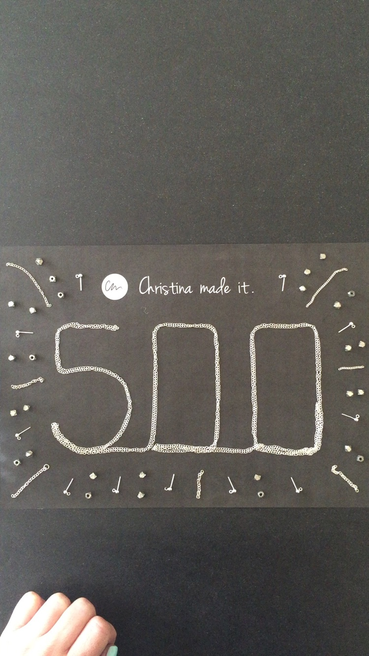 500 sign made from silver chains, beads and earrings