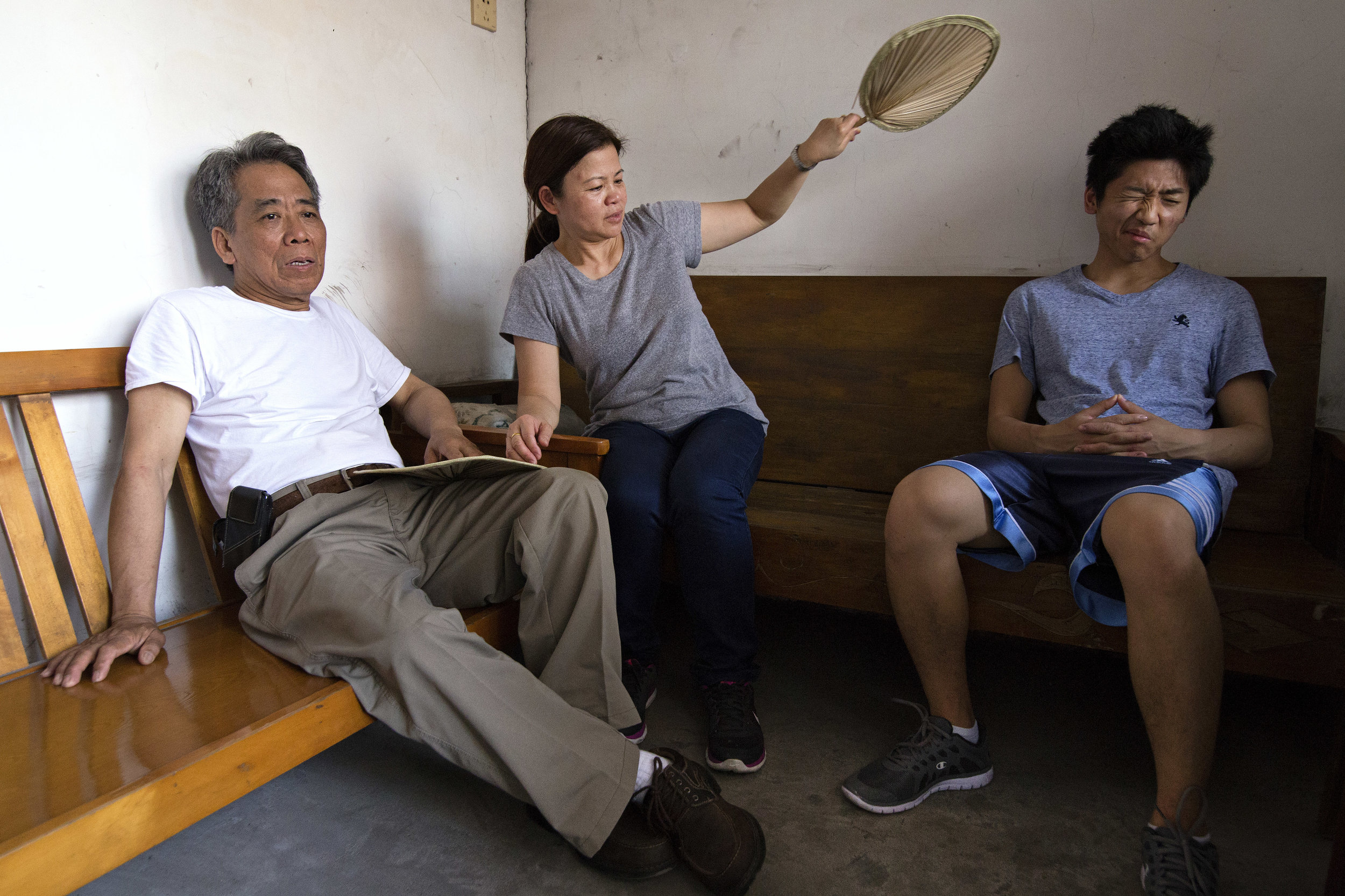 "Father, mother and my brother, Ted, sit on wooden benches handcrafted by Gongong. ""This was also Gonggong's bed. This is where he slept,"" Mother remarks, referring to the bench on the right."