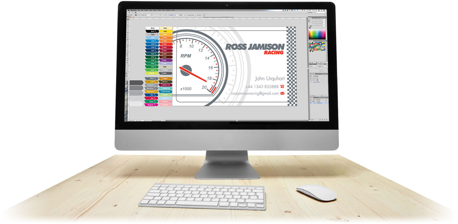 A large image of an iMac, keyboard and mouse situated on a wooden desk. On the screen is the source artwork for a business card created as part of the free design service