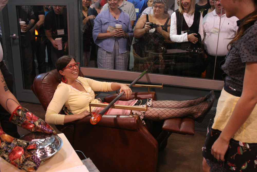 """Jessica Jane Julius, in recliner glass blowing bench, Corning NY during performance """"TV Dinner""""."""